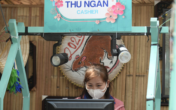 A staff is seen wearing face mask while working at Nguyen Van Binh book street in Ho Chi Minh City's District 1. Photo: Tuoi Tre/ Tu Trung