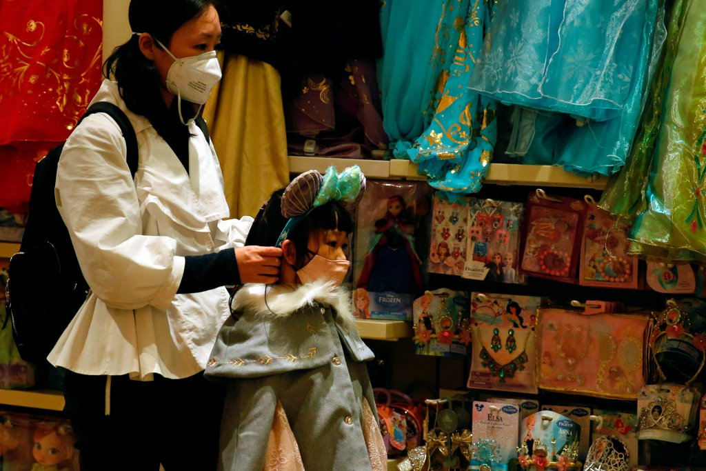 A child wears mask as she tries a themed ears at a souvenir shop in Disneyland hotel after Hong Kong Disneyland that has been closed, following the coronavirus outbreak in Hong Kong, China January 26, 2020. REUTERS/Tyrone Siu