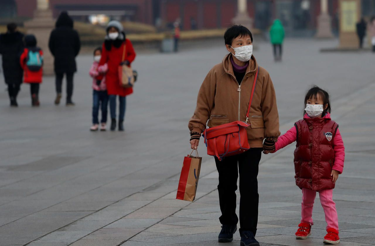 People wearing face masks walk at the Tiananmen Gate, as the country is hit by an outbreak of the new coronavirus, in Beijing, China January 27, 2020. Photo: Reuters