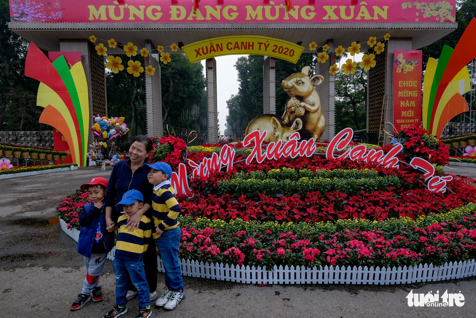 A family poses for a picture beside a bed of Tet flowers in Hanoi. Photo: Nam Tran / Tuoi Tre