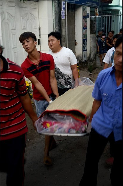 Local residents carry a body to the ambulance. Photo: Ai Nhan / Tuoi Tre