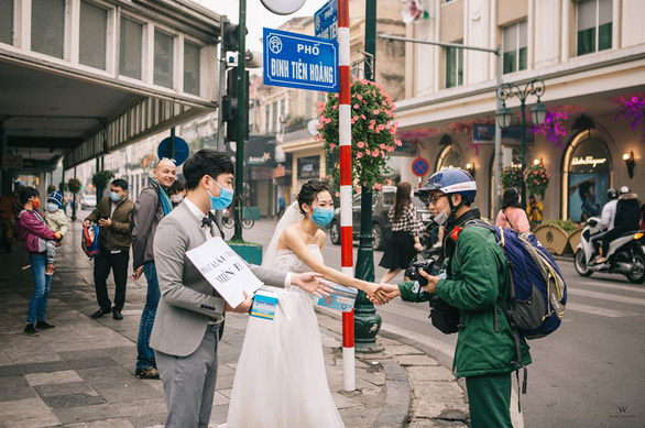 <em>A couple gives away medical masks to commuters and passers-by on a street in Hanoi for their pre-wedding photos in this picture uploaded on Facebook.</em>