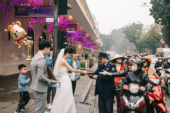 A couple gives away medical masks to commuters and passers-by on a street in Hanoi for their pre-wedding photos in this picture uploaded on Facebook