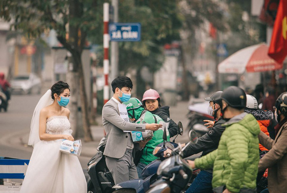 Couple gives away face masks on Hanoi streets in viral pre-wedding photos