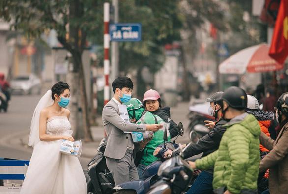 Пара раздает маски на улицах Ханоя на предсвадебных фотографиях (ФОТО)