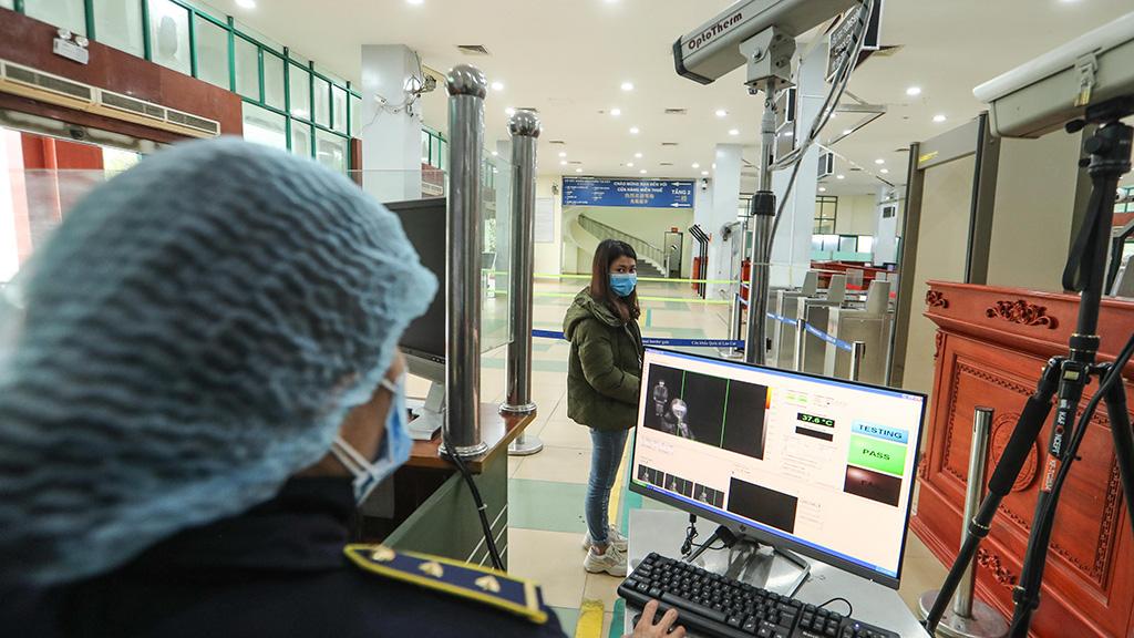 A Vietnamese citizen has her body temperature measured at the Lao Cai Border Gate.