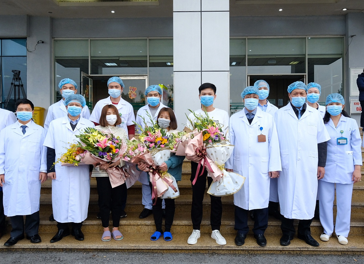Three recovered novel coronavirus patients take a photo with doctors at the National Hospital for Tropical Disease in Hanoi, February 10, 2020. Photo: Nam Tran / Tuoi Tre