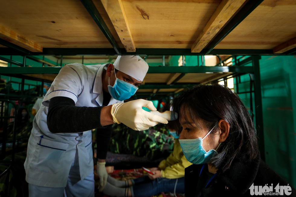 A medical staff checks the body temperature of a woman at the Military School of Lao Cai Province in northern Vietnam. Photo: Nguyen Khanh / Tuoi Tre