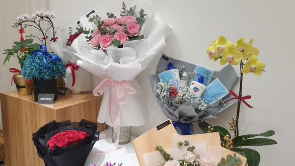 A bouquet of face masks and bottles of hand sanitizer is placed next to flower bouquets in this photo taken at a florist's in Ho Chi Minh City, Vietnam, February 2020. Photo: Bong Mai / Tuoi Tre