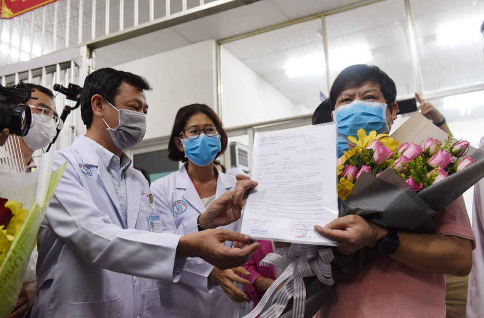 Li Ding (R) receives a certificate of discharge from Nguyen Tri Thuc, director of Cho Ray Hospital in Ho Chi Minh City, Vietnam, February 12, 2020. Photo: Duyen Phan / Tuoi Tre