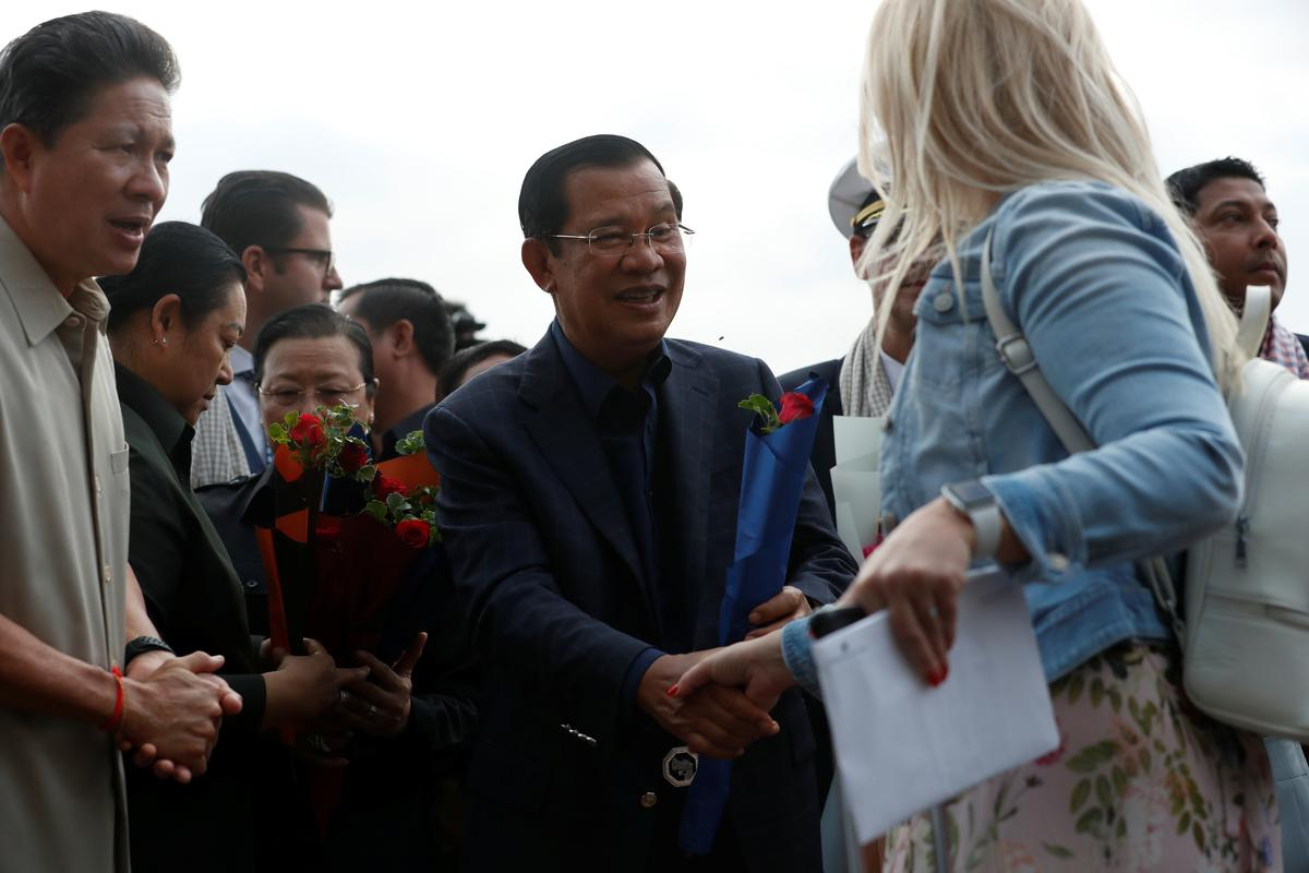 Cambodia's Prime Minister Hun Sen welcomes a passenger of MS Westerdam, a cruise ship that spent two weeks at sea after being turned away by five countries over fears that someone aboard might have the coronavirus, as it docks in Sihanoukville, Cambodia February 14, 2020. Photo: Reuters