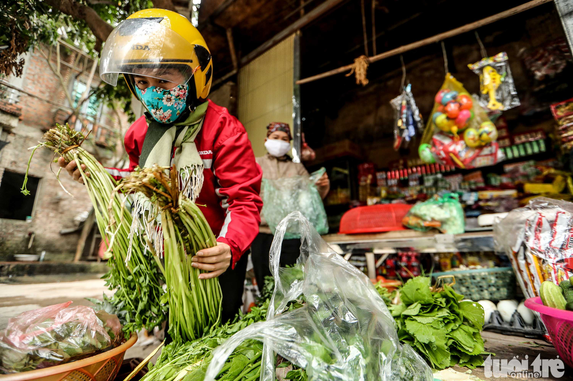 A resident buys groceries at a vegetable stand owned by Nguyen Thi Thang in Ai Van Village in Son Loi Commune, Binh Xuyen District, Vinh Phuc Province, Vietnam. Photo: Nguyen Khanh / Tuoi Tre