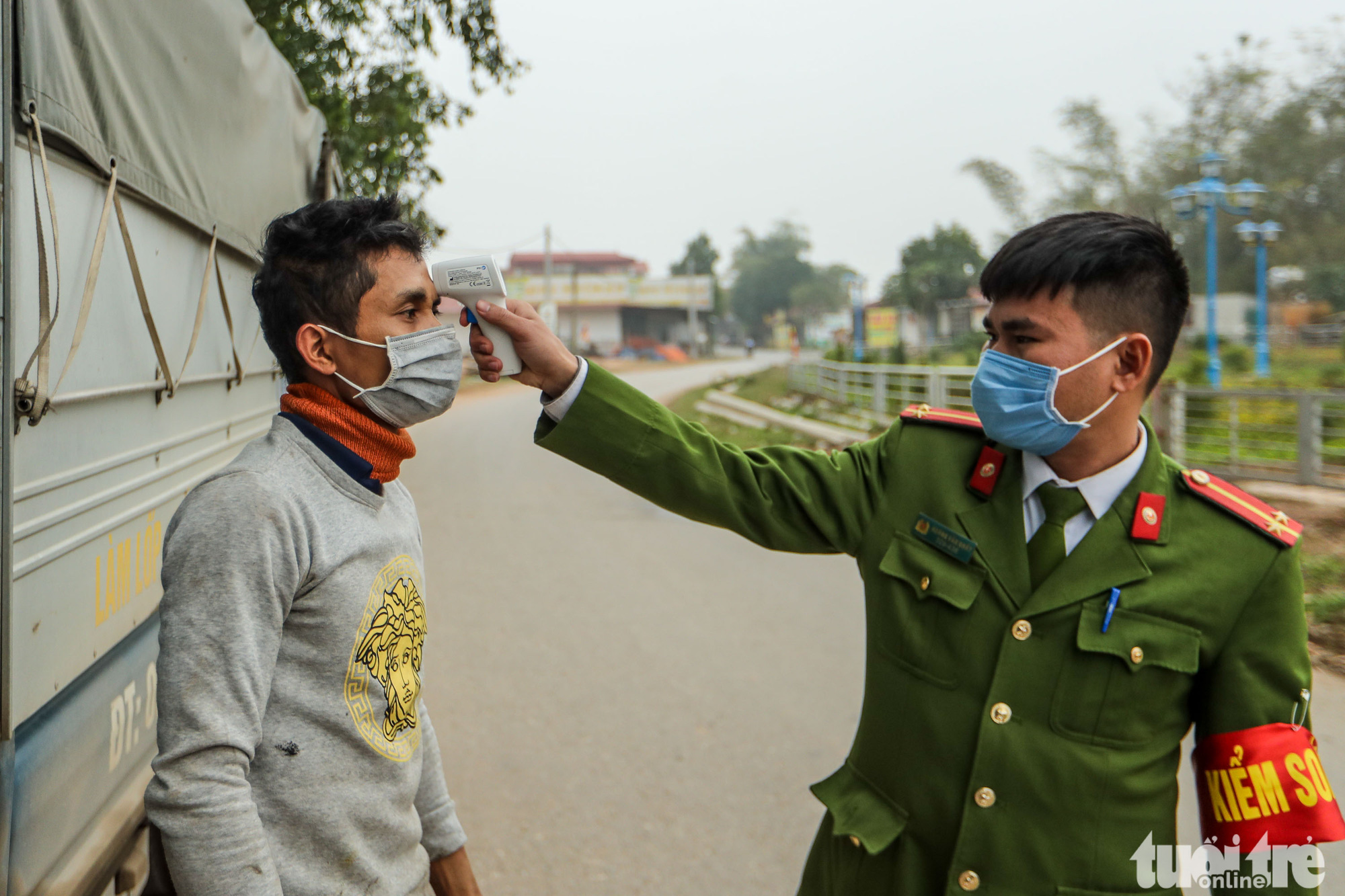 A man has his body temperature checked by a police officer at a checkpoint set up at an entrance to Son Loi Commune in Binh Xuyen District, Vinh Phuc Province, Vietnam in this photo taken on February 11, 2020. Photo: Nguyen Khanh / Tuoi Tre