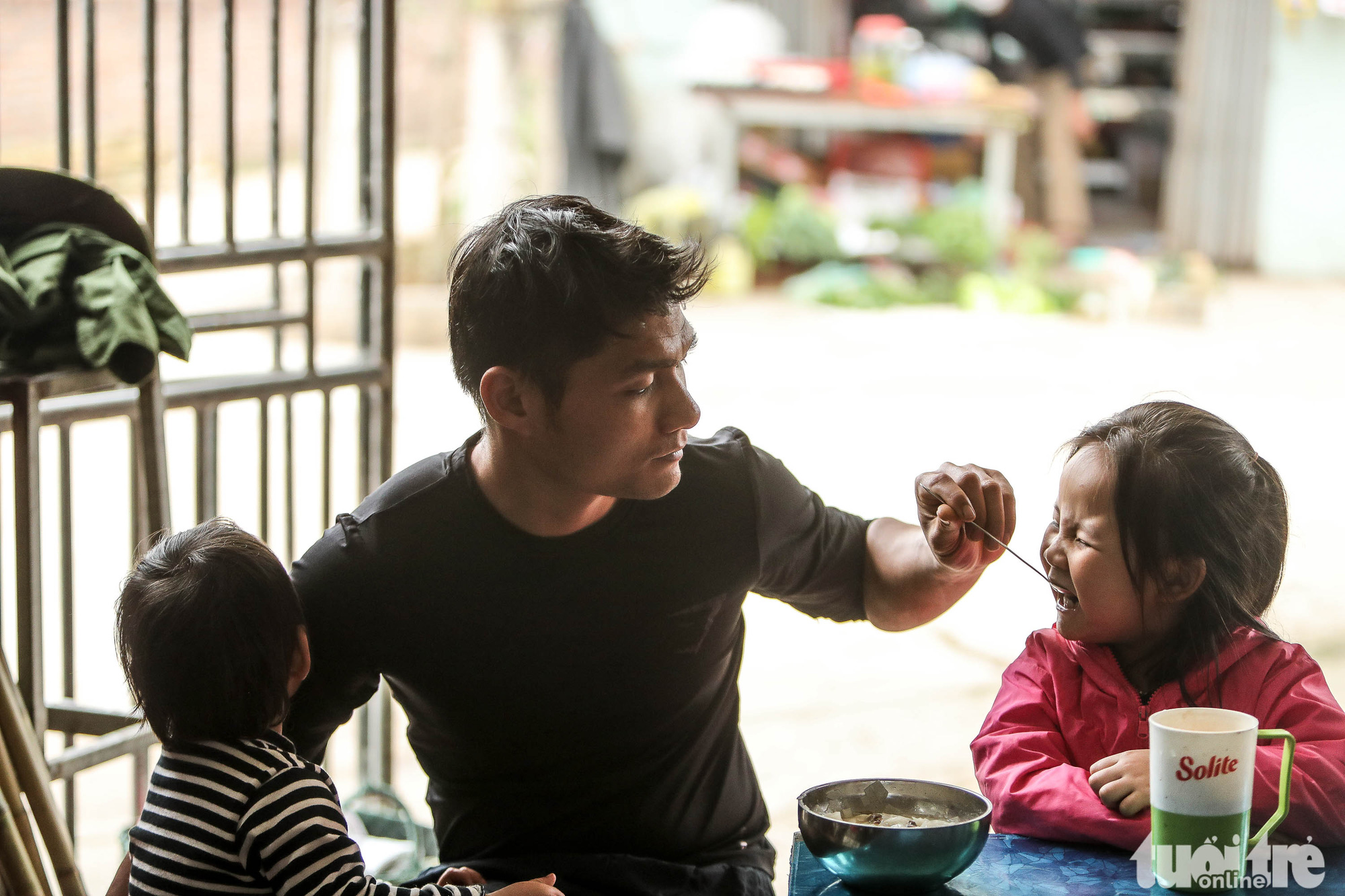 Nguyen Van Huu, a steel factory worker, feeds his children at their home in Son Loi Commune in Binh Xuyen District, Vinh Phuc Province, Vietnam as he is under home quarantine on his company's request in this photo taken on February 11, 2020. Photo: Nguyen Khanh / Tuoi Tre