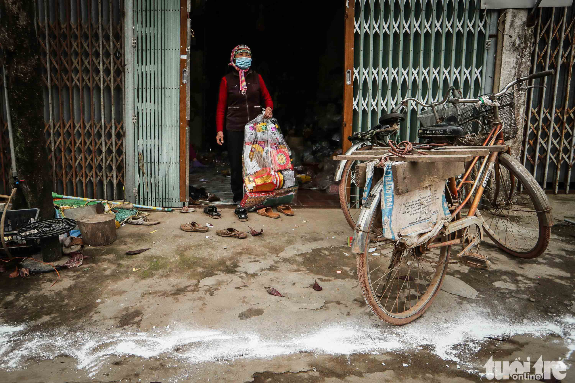 Pham Thi Trang, a resident in Ai Van Village in Son Loi Commune, Binh Xuyen District, Vinh Phuc Province, Vietnam, sprinkles calcium hydroxide in front of her house for disinfection on February 11, 2020. Photo: Nguyen Khanh / Tuoi Tre