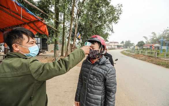 A man has his body temperature checked at a checkpoint set up at an entrance to Son Loi Commune in Binh Xuyen District, Vinh Phuc Province, Vietnam in this photo taken on February 11, 2020. Photo: Nguyen Khanh / Tuoi Tre