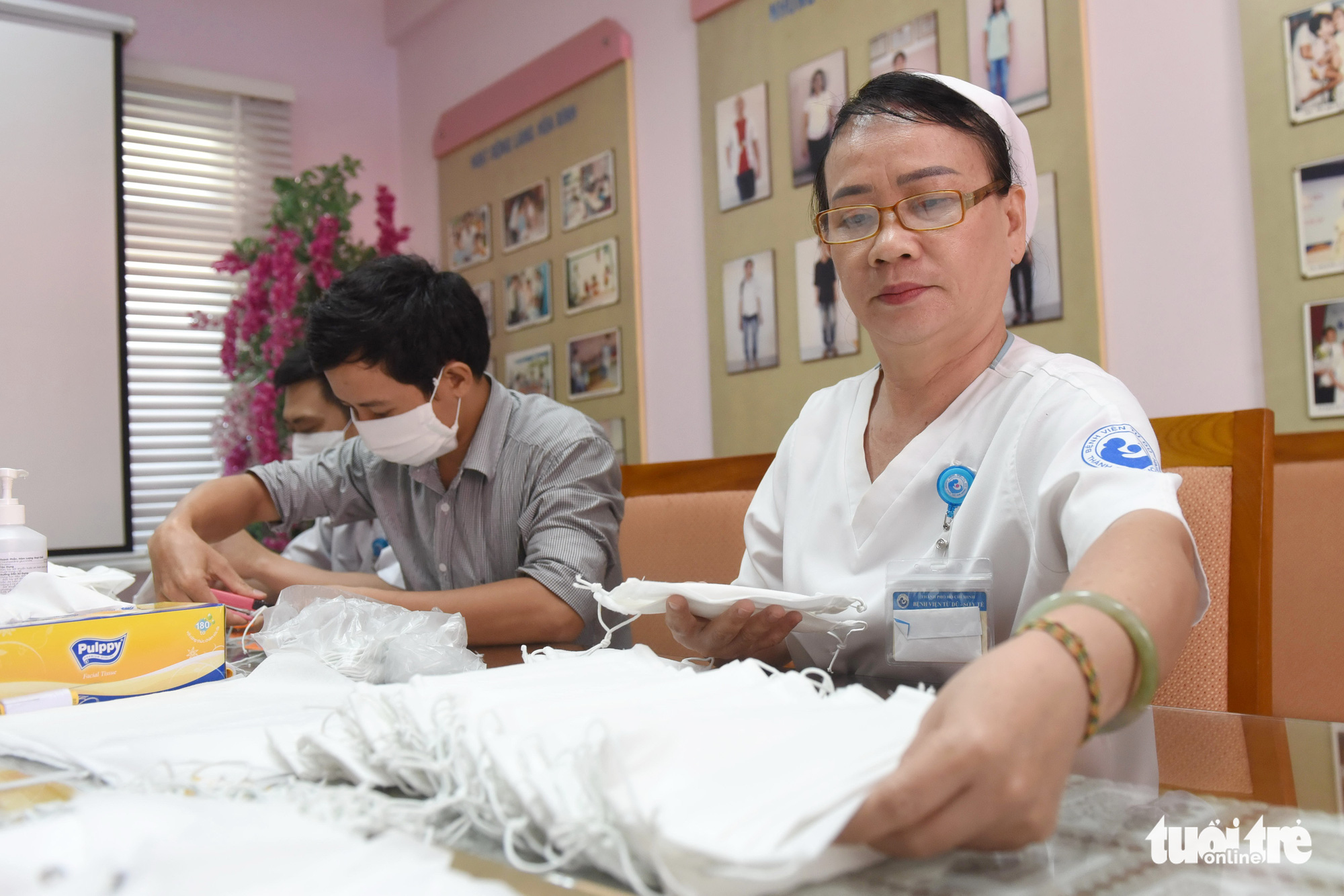 Doan Thi Thanh, deputy head of the rehabilitation ward at Tu Du Maternity Hospital in Ho Chi Minh City, organizes stacks of face masks made by her colleagues, February 13, 2020. Photo: Duyen Phan / Tuoi Tre