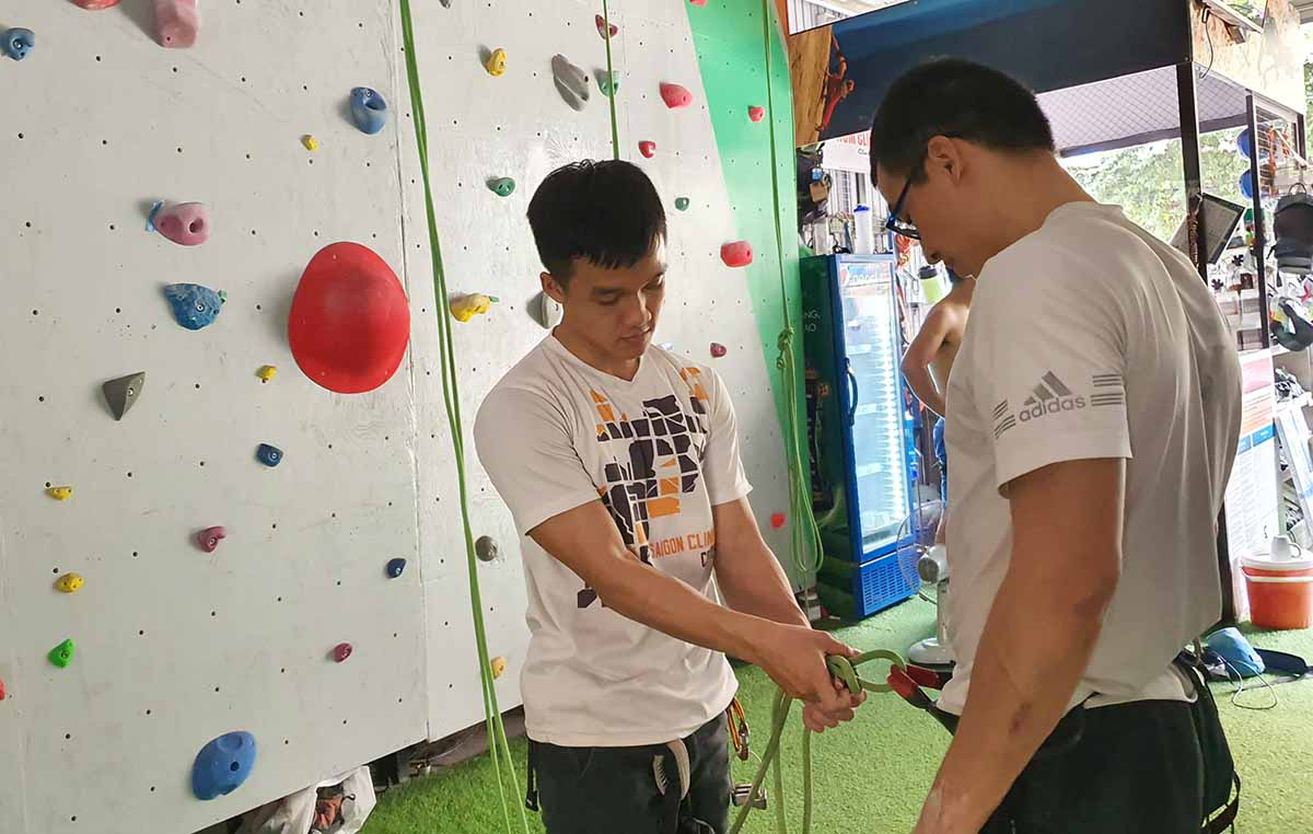 Nguyen Tran Trung Hau (left), a sophomore undergraduate at Ho Chi Minh City University of Medicine and Pharmacy, works part-time at Saigon Climbing Center in Binh Thanh District, Ho Chi Minh City. Photo: Me Thuan / Tuoi Tre