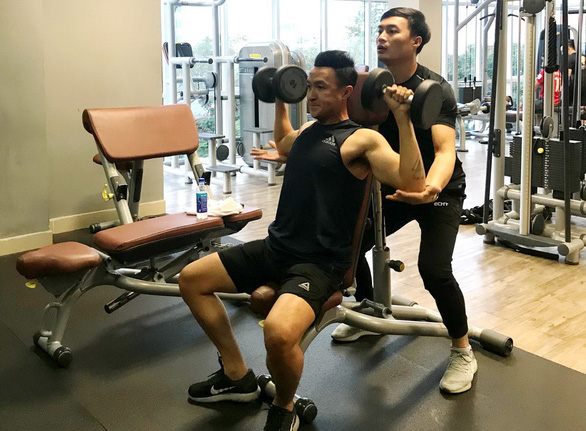 Television anchor Truong Viet Phong (sitting) works out with dumbbells at a gym in Ho Chi Minh City, Vietnam in this provided photo.