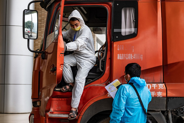 A truck is brought back to a Chinese driver (in blue suit) after the delivery is complete.