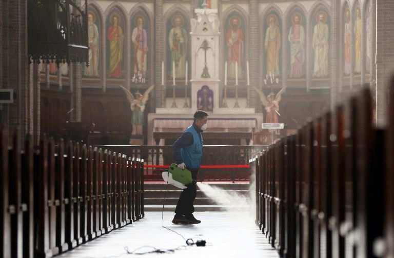 A staff member sprays disinfectant as part of preventive measures against the spread of the COVID-19 coronavirus, at Myeongdong Catholic Cathedral in Seoul. Photo: AFP