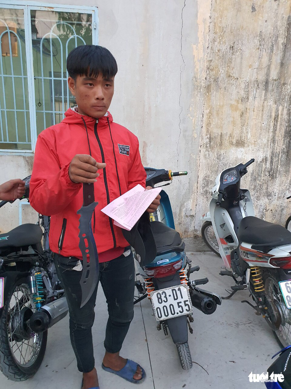 One of the suspects carries along a machete. Photo: H. T. / Tuoi Tre