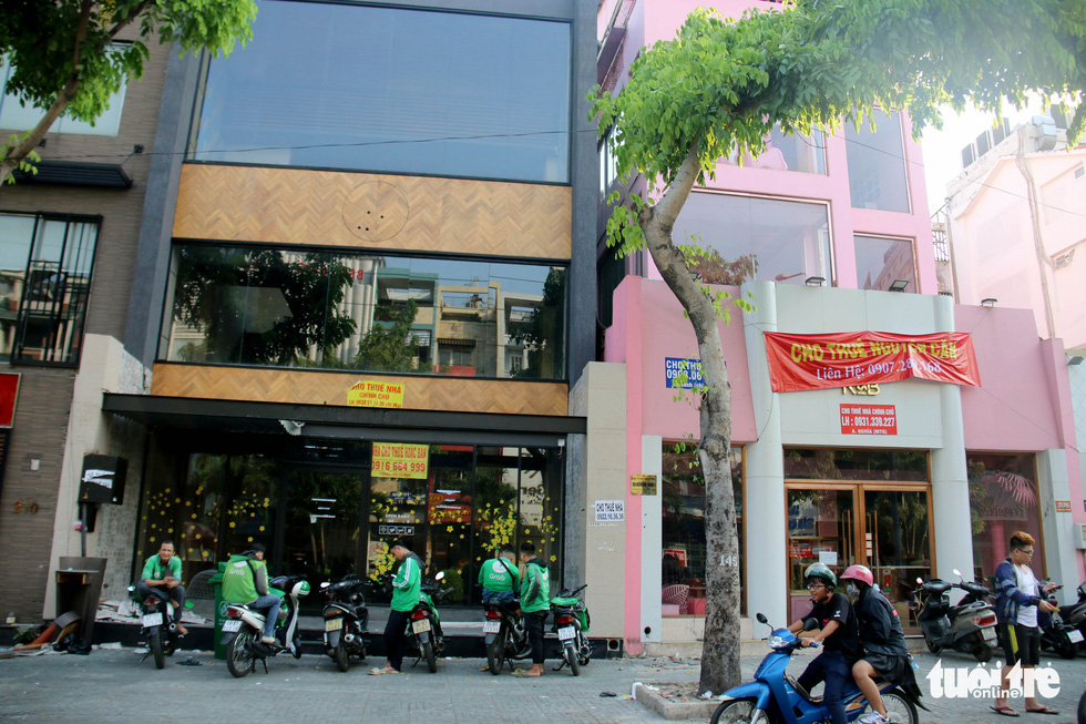 GrabBike drivers park their motorbikes in front of a building, where a coffee shop once operated, that is now up for rent on Phan Xich Long Street in Phu Nhuan District, Ho Chi Minh City. Photo: Ngoc Hien / Tuoi Tre