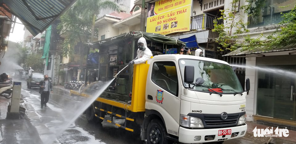 Authorities in protective suit are spraying disinfectant at the neighborhood in Hanoi's Ba Dinh District where Vietnam's 17th COVID-19 patient resides, on March 7, 2020. Photo: Ha Thanh/ Tuoi Tre News