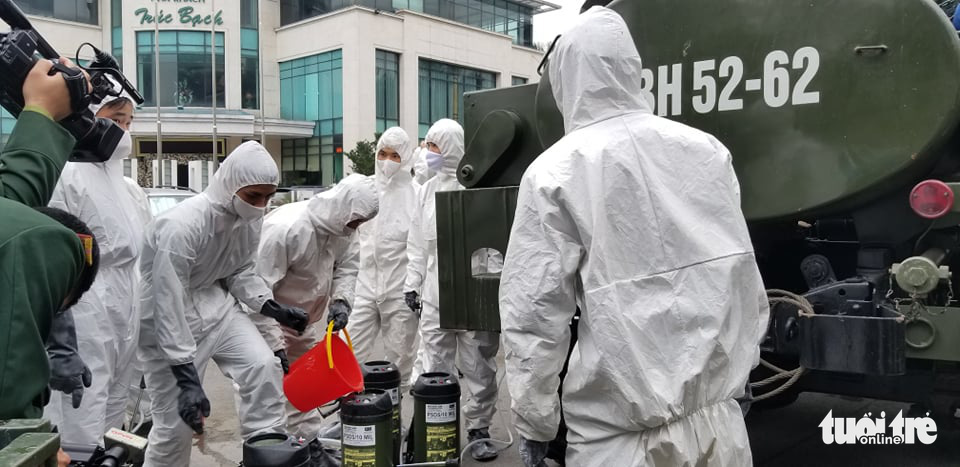 Authorities in protective suit are preparing for the disinfection at the neighborhood in Hanoi's Ba Dinh District where Vietnam's 17th COVID-19 patient resides, on March 7, 2020. Photo: Ha Thanh/ Tuoi Tre News