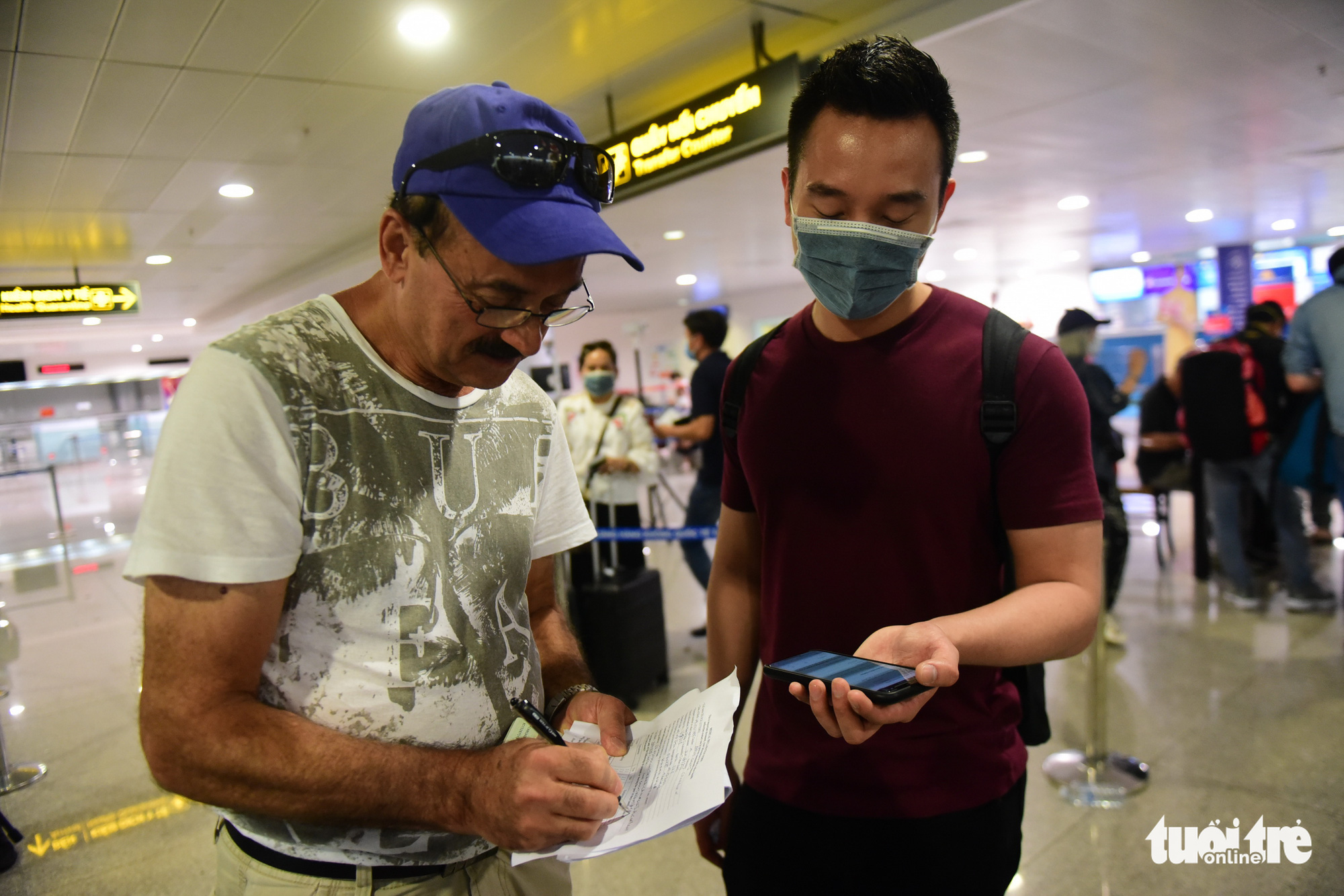A Vietnamese passenger (right) helps a Canadian national complete the declaration form at Tan Son Nhat International Airport in Ho Chi Minh City. Photo: Quang Dinh / Tuoi Tre