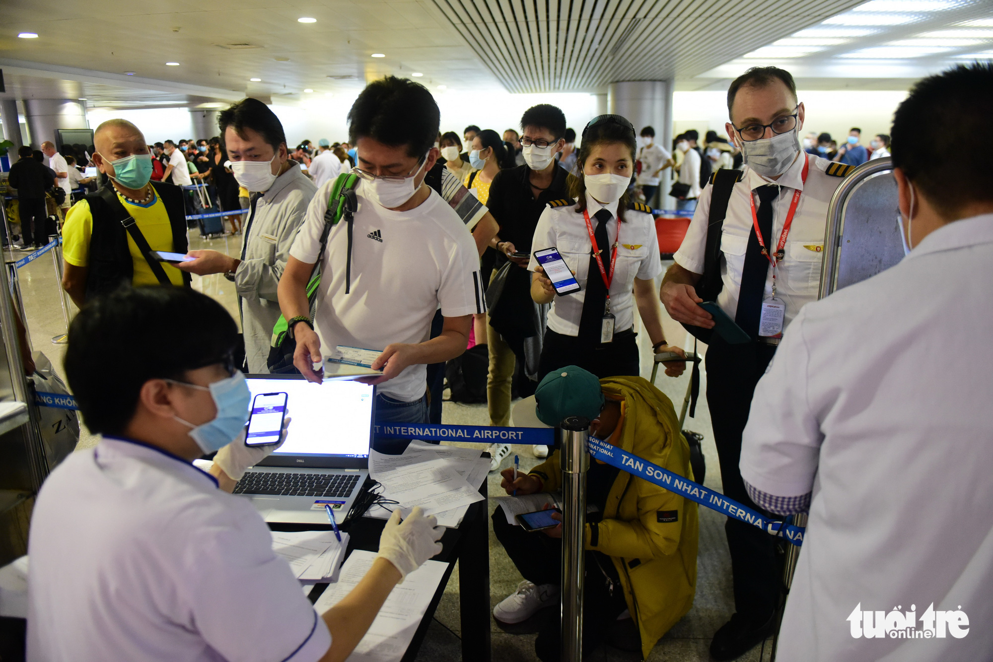 A female pilot shows a completed online health declaration form to a quarantine officer at Tan Son Nhat International Airport in Ho Chi Minh City, Vietnam, March 9, 2020. Photo: Quang Dinh / Tuoi Tre