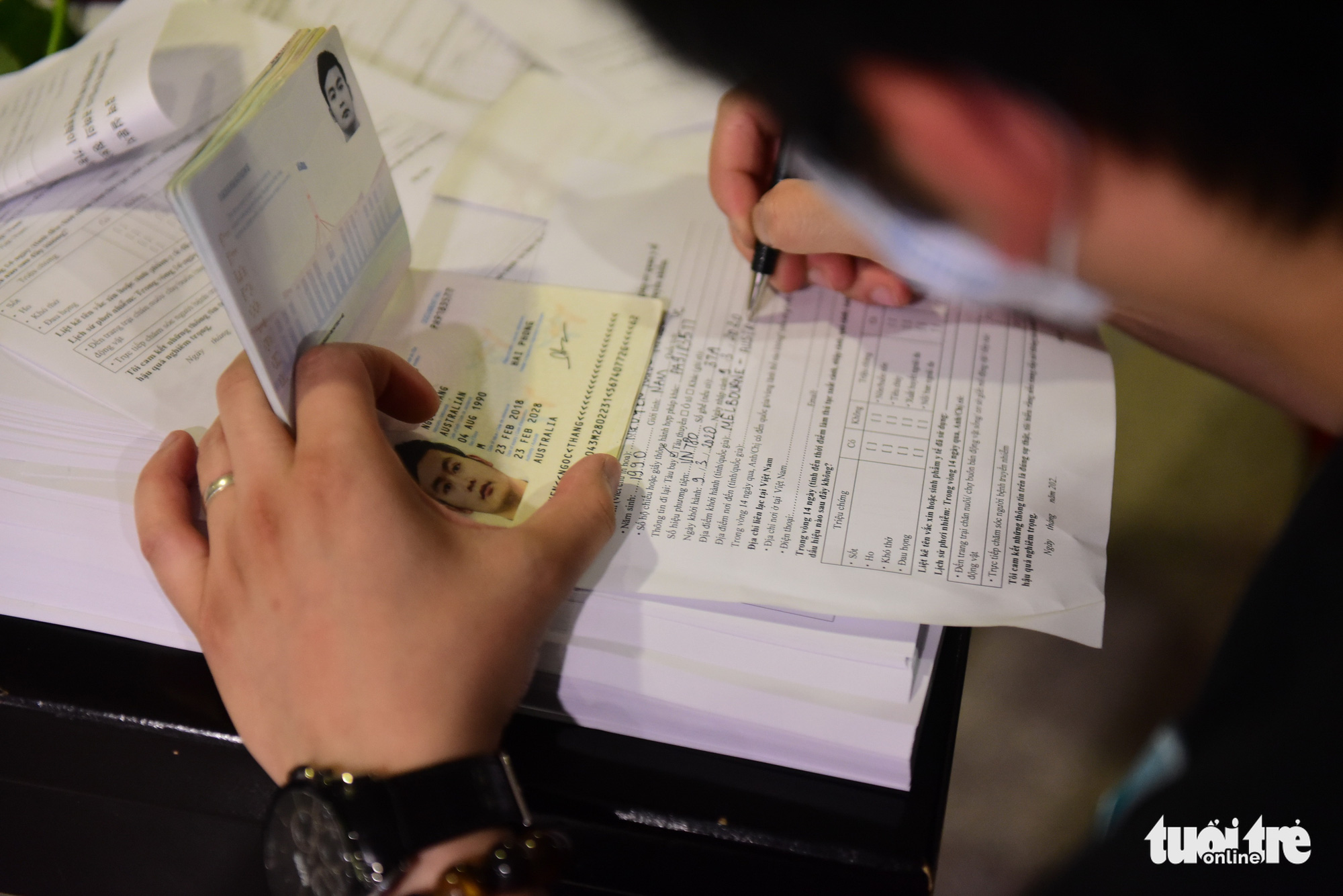 A man fills out his medical declaration form at Tan Son Nhat International Airport in Ho Chi Minh City, Vietnam. Photo: Quang Dinh / Tuoi Tre