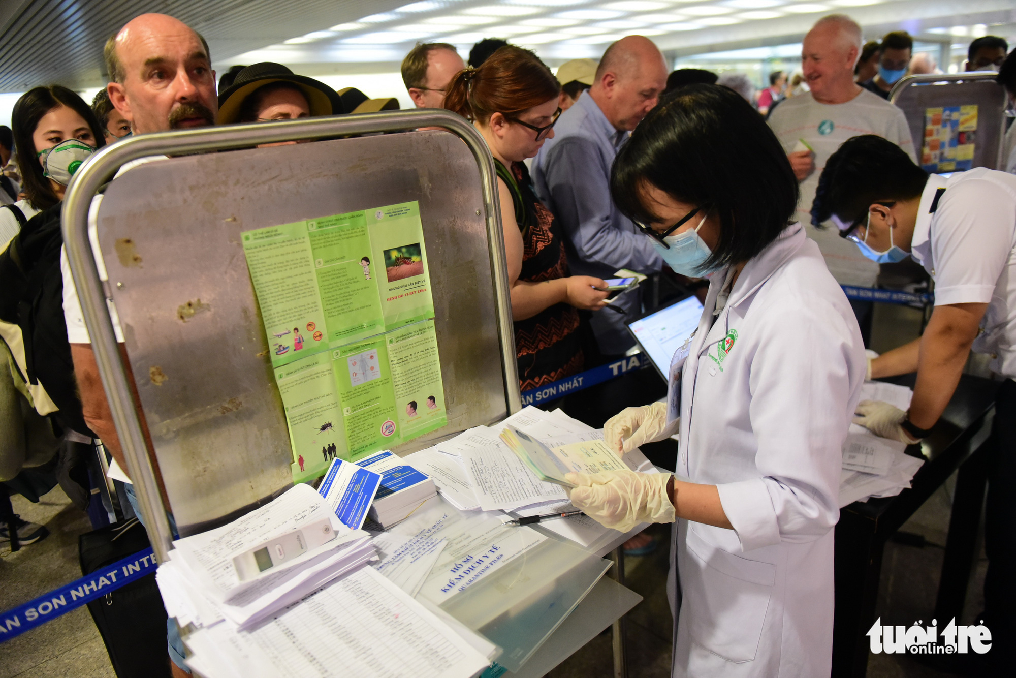 Quarantine officers organize medical declaration forms from passengers at Tan Son Nhat International Airport in Ho Chi Minh City. Photo: Quang Dinh / Tuoi Tre