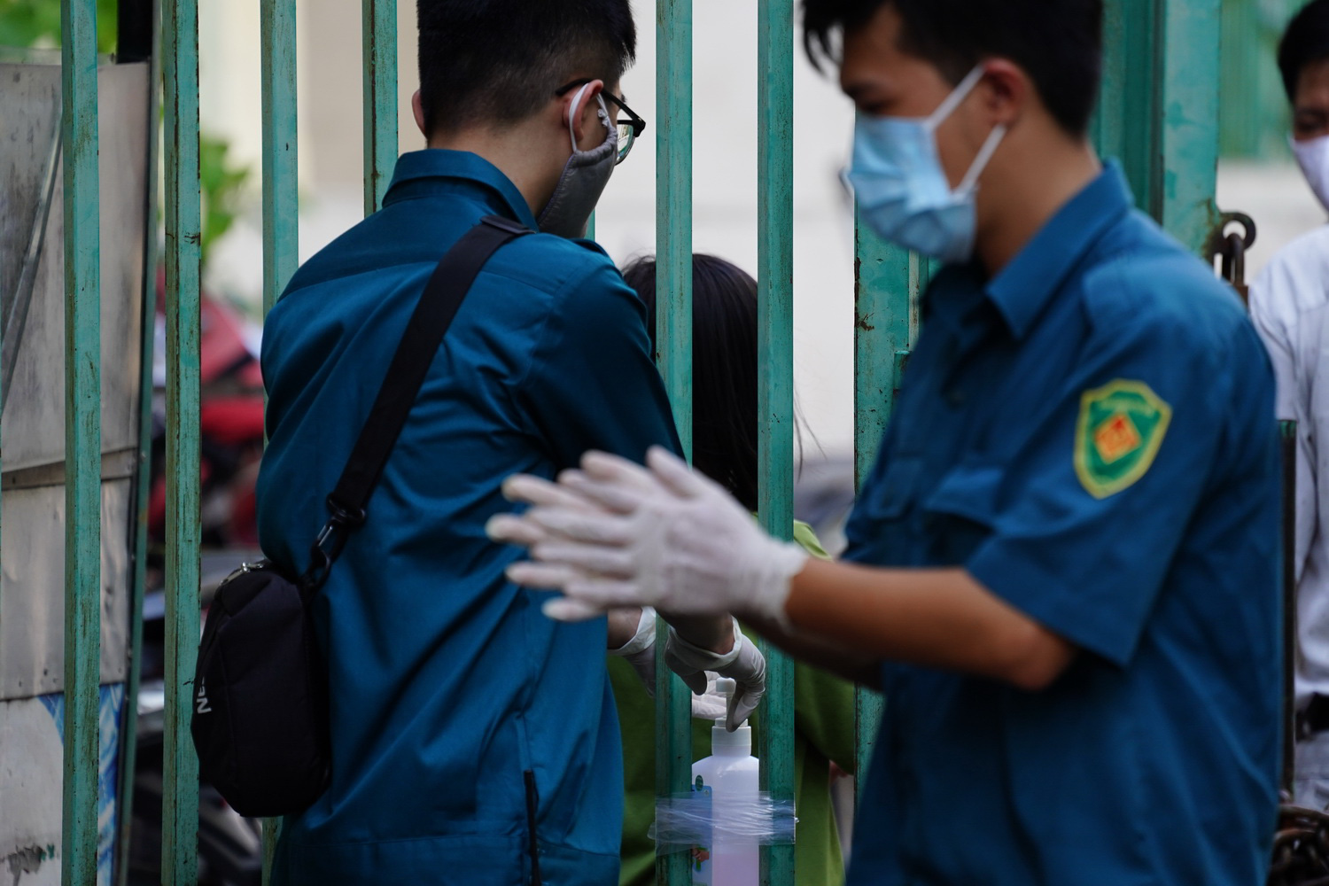 Two men who are tasked with guarding the apartment building wash their hands during the job. Photo: Ly Nguyen / Tuoi Tre