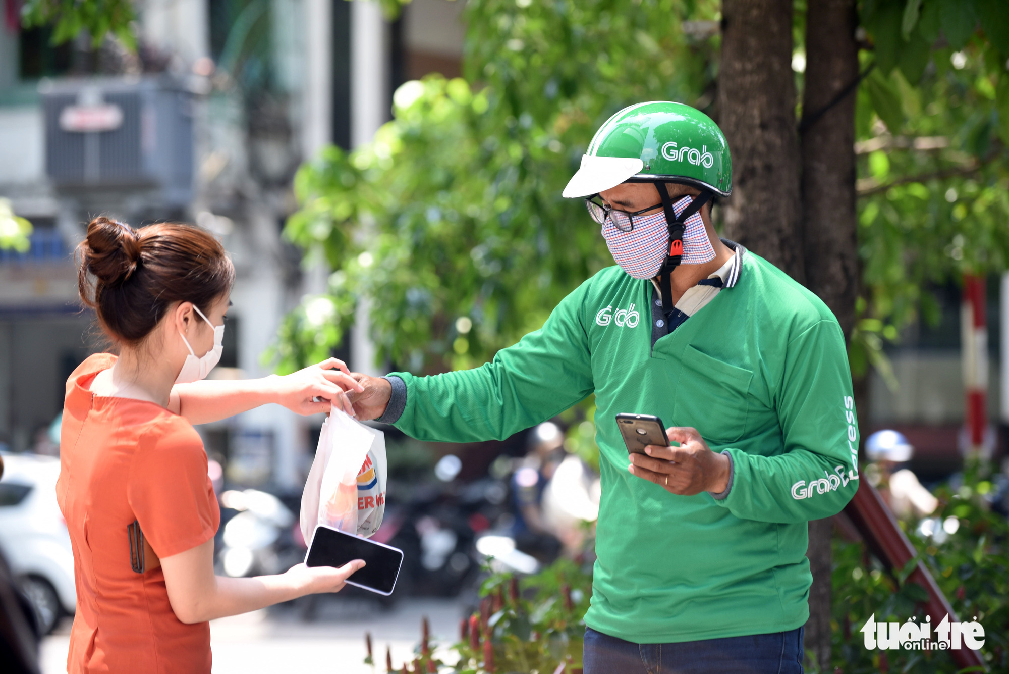An office worker receives ordered food from a Grab delivery driver in Ho Chi Minh City, Vietnam. Photo: Duyen Phan / Tuoi Tre