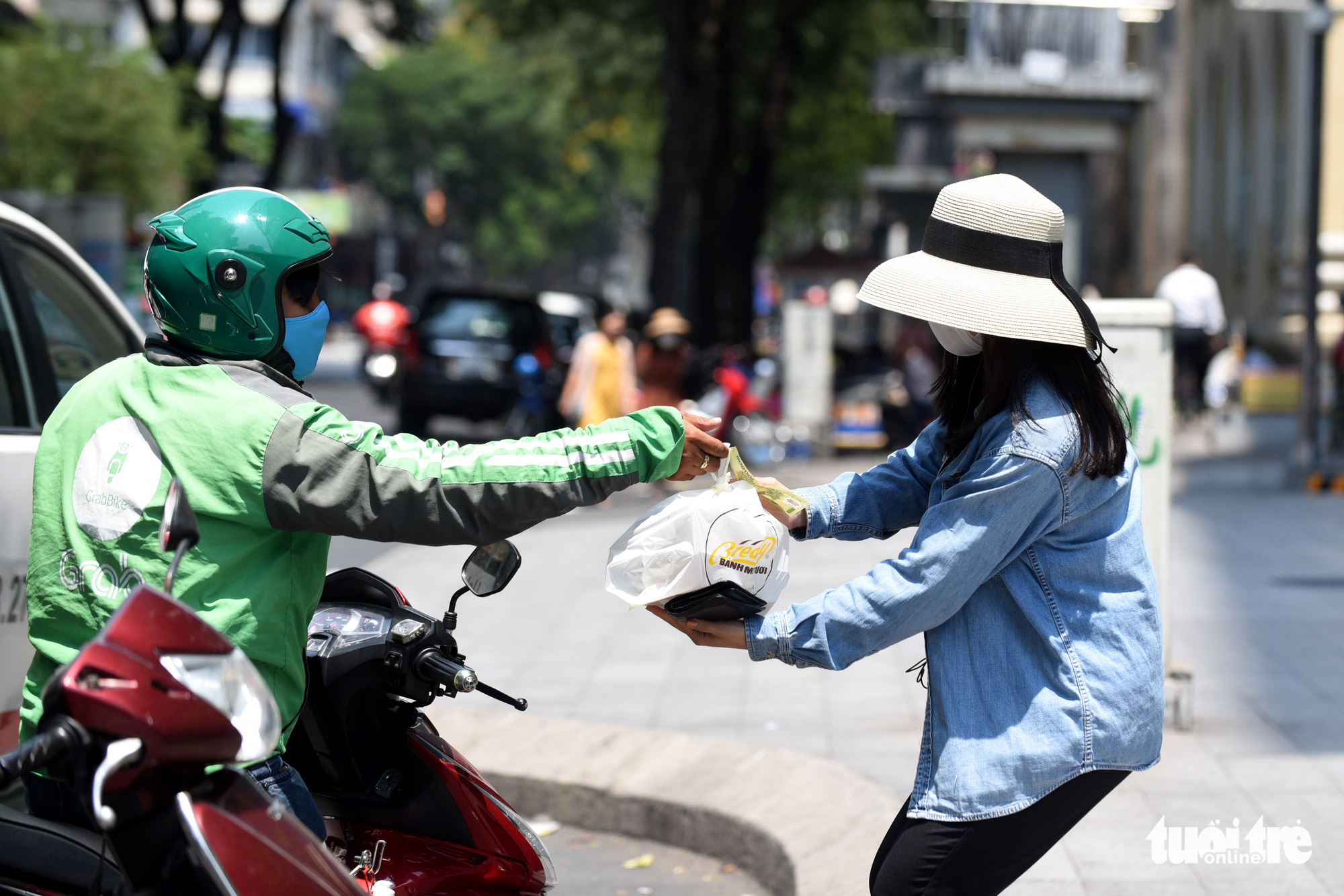 An office worker receives food from a Grab driver in Ho Chi Minh City, Vietnam. Photo: Duyen Phan / Tuoi Tre