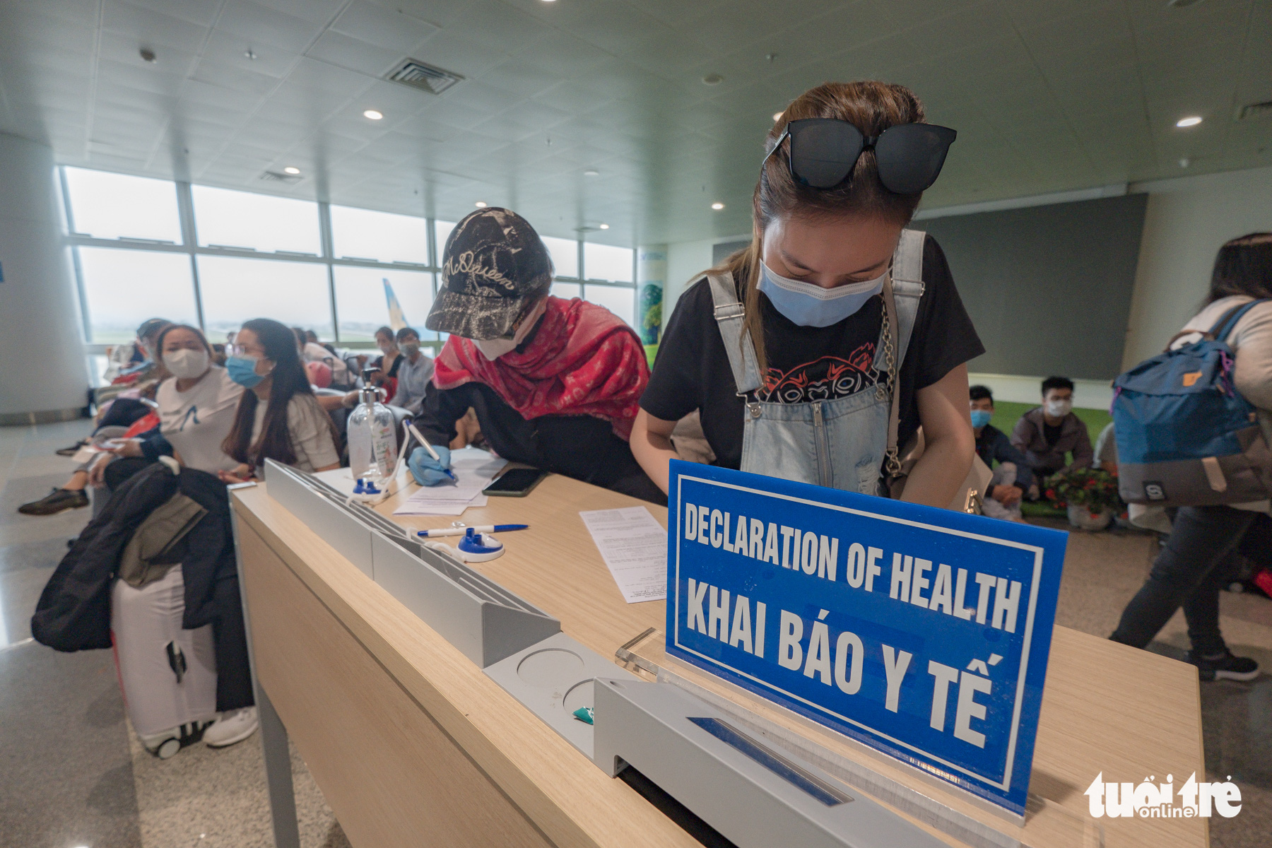 People fill out health declaration forms upon their arrival at Noi Bai International Airport in Hanoi, Vietnam, March 18, 2020. Photo: Nam Tran / Tuoi Tre