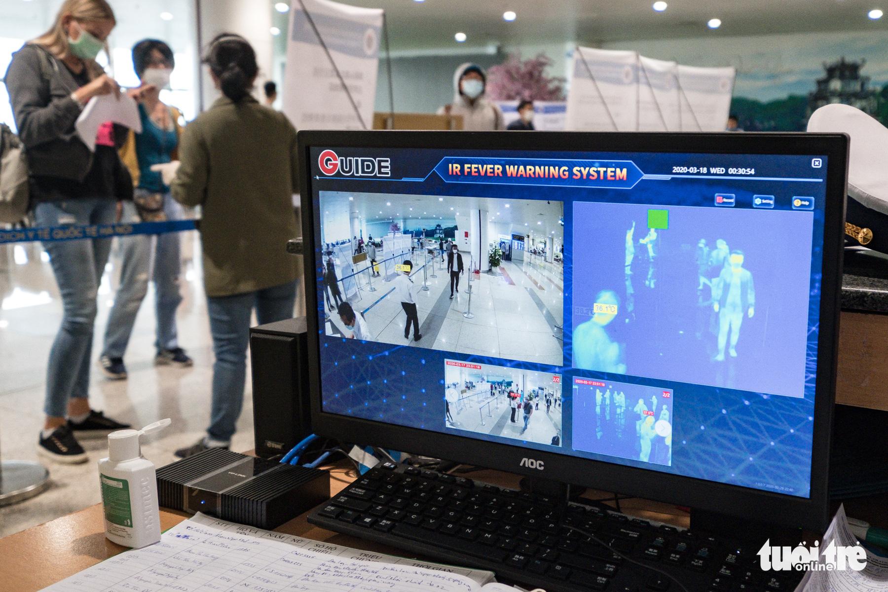 Passengers have their body temperature monitored at Noi Bai International Airport in Hanoi, Vietnam, March 18, 2020. Photo: Nam Tran / Tuoi Tre