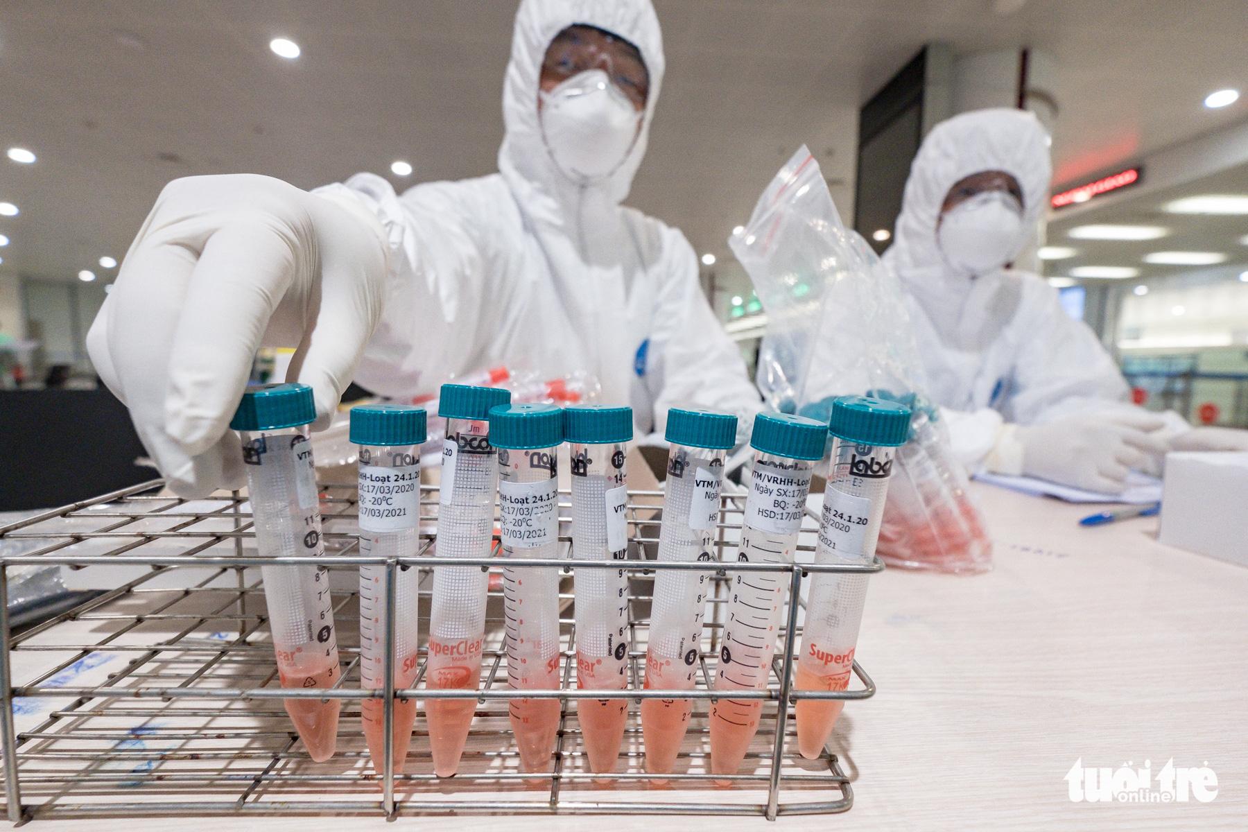A medical worker prepares sample tubes for sampling arrivals at Noi Bai International Airport in Hanoi, Vietnam, March 18, 2020. Photo: Nam Tran / Tuoi Tre