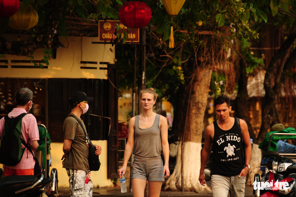Two foreign tourists are seen walking in the central city of Hoi An without face masks. Photo: B.D/Tuoi Tre