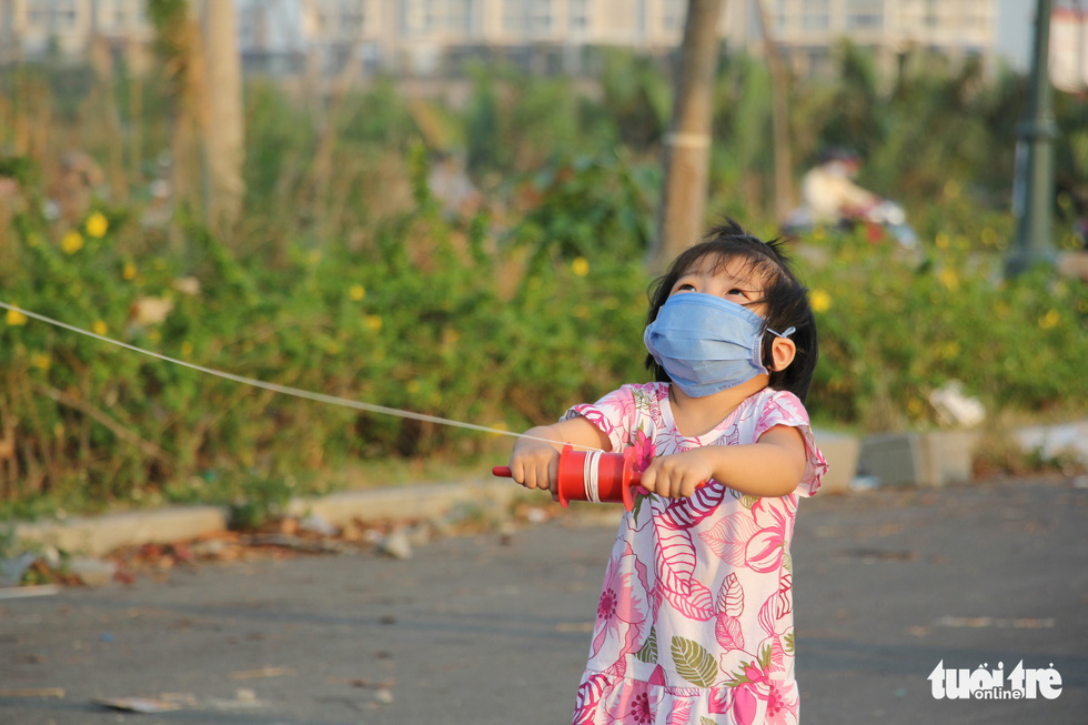 A girl wearing a face mask flies a kite at a kite field in District 2, Ho Chi Minh City, March 2020. Photo: Mai Thuong / Tuoi Tre