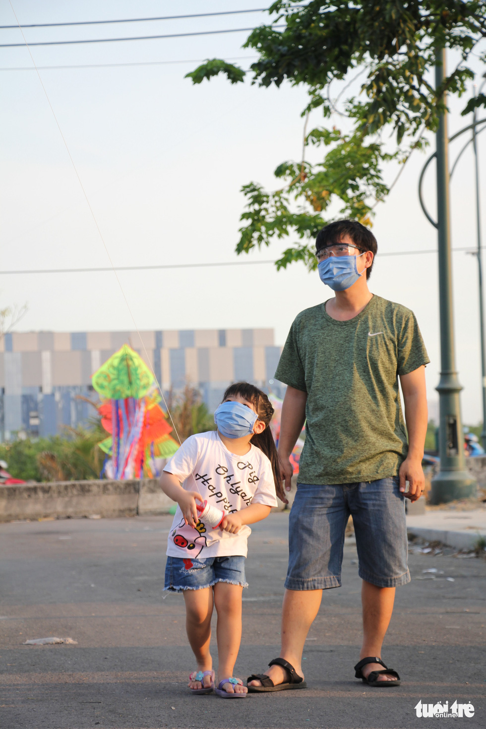 A girl and her father wearing face masks fly a kite at a kite field in District 2, Ho Chi Minh City, March 2020. Photo: Mai Thuong / Tuoi Tre