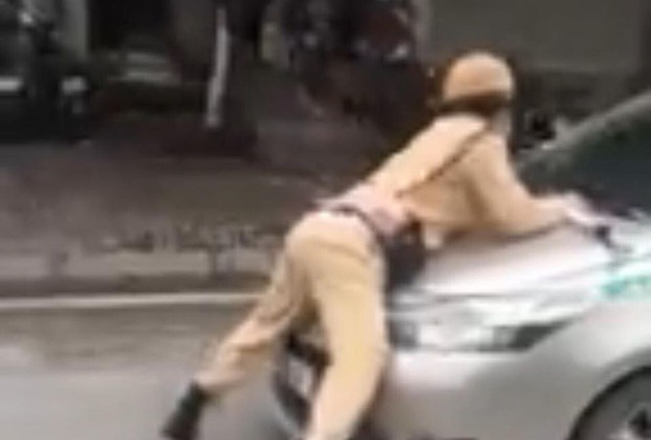 Taxi driver detained for taking traffic cop for ride on hood of car in Hanoi