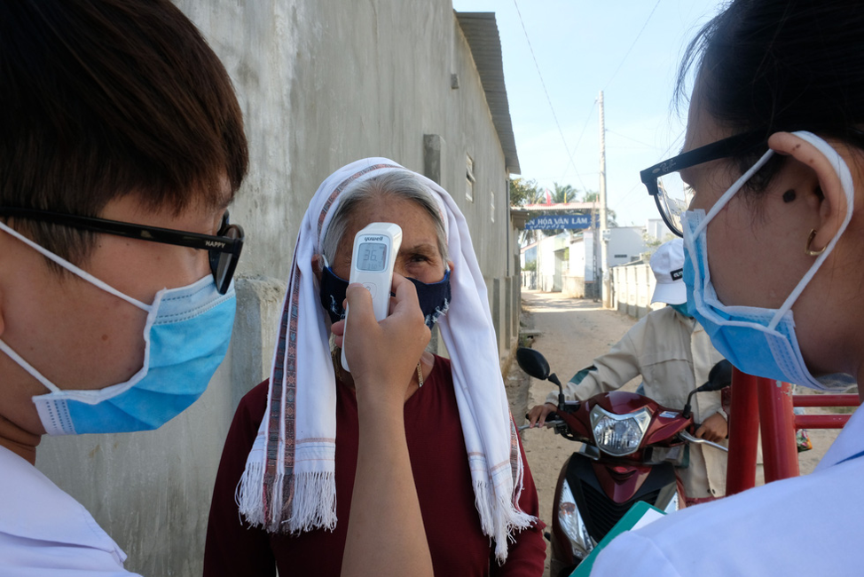 Medical workers check the body temperature of a resident in Van Lam 3 Village, Ninh Thuan Province, Vietnam. Photo: Dinh Cuong / Tuoi Tre