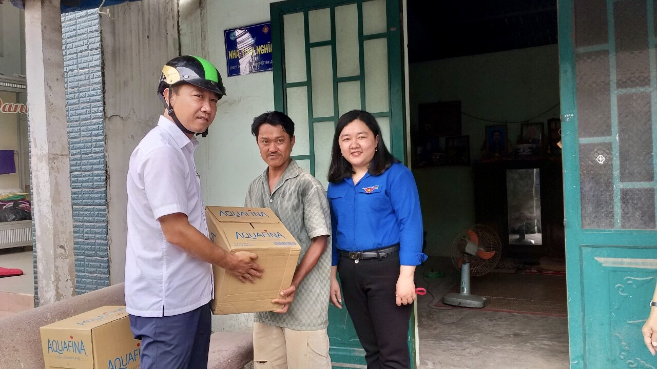A Ben Tre Youth Union official (left) hands bottled water  donated by Suntory PepsiCo Vietnam to a household in Ben Tre Province, Vietnam, March 9, 2020.