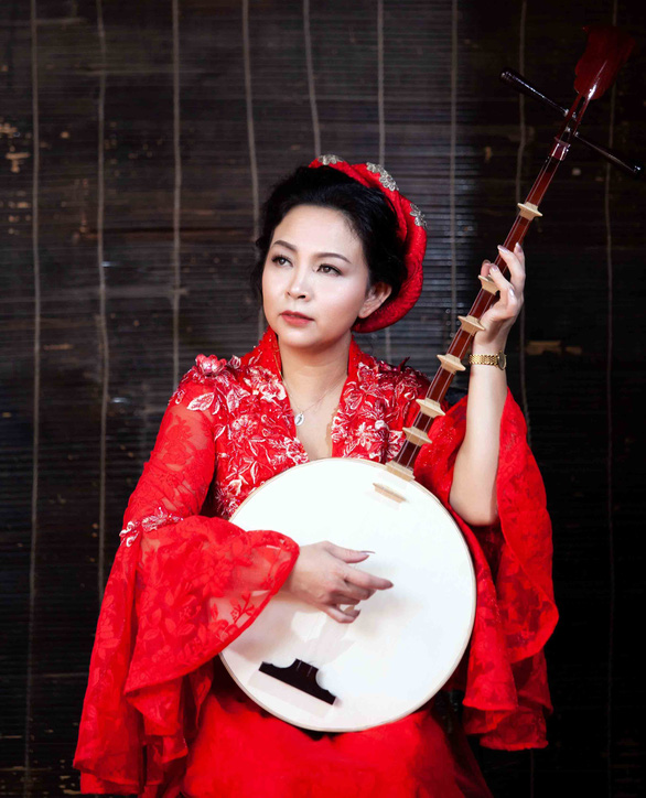 Artist Tran Thi Truc Tien plays the 'don kim,' a traditional Vietnamese two-stringed musical instrument, in this supplied photo.