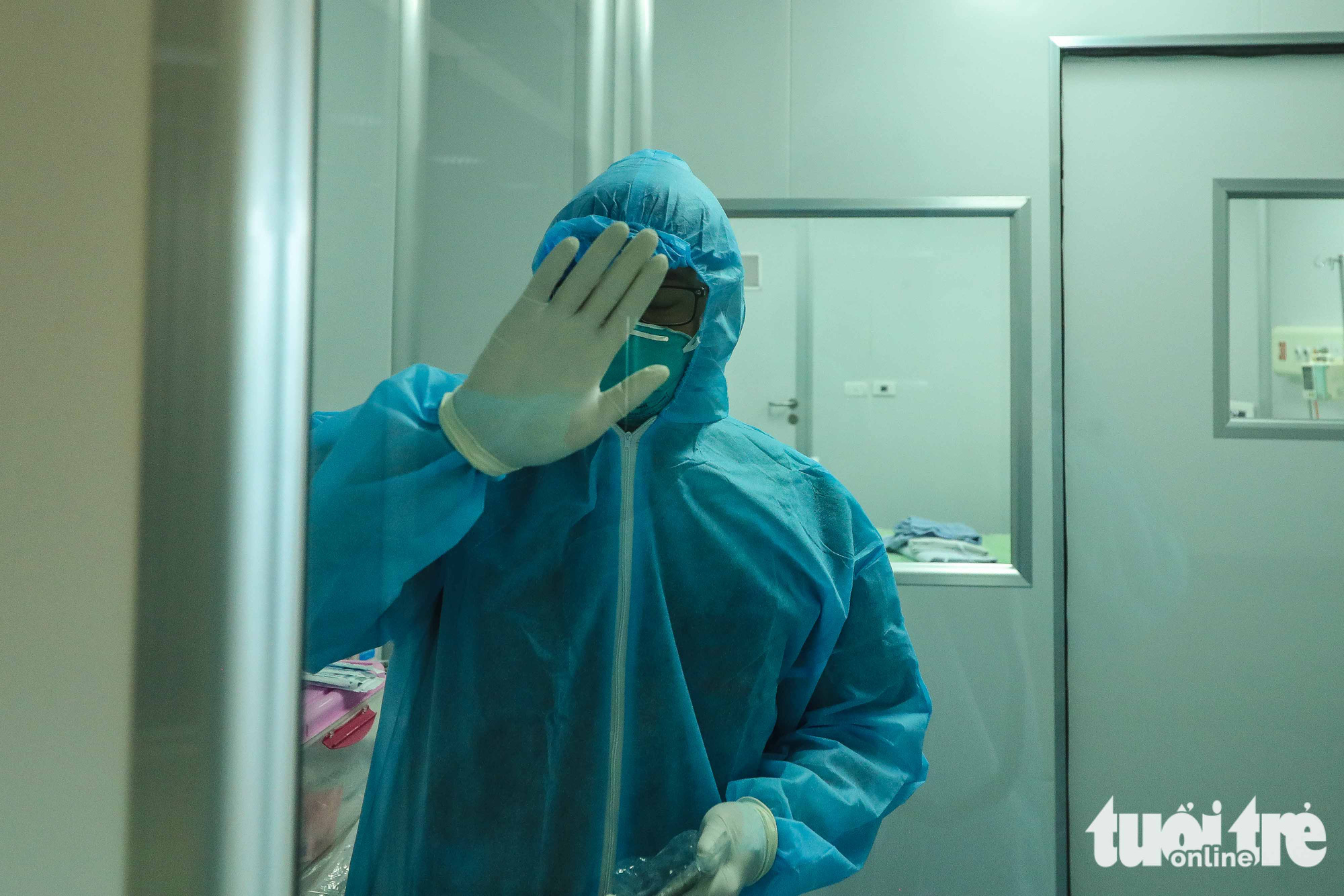 A doctor waves from inside a negative pressure room at the National Hospital for Tropical Diseases in Dong Anh District in Hanoi, Vietnam. Photo: Nguyen Khanh / Tuoi Tre