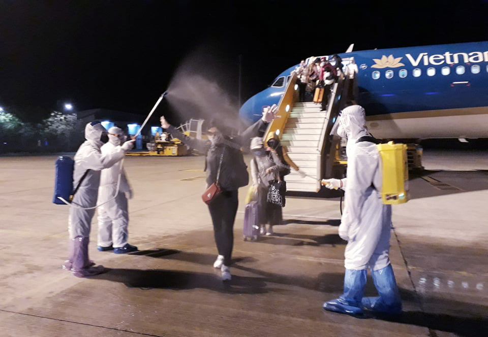 Passengers are disinfected after the deboarding a charter flight that lands in Can Tho City, Vietnam, March 24, 2020.  Photo: Khuong Xuan / Tuoi Tre