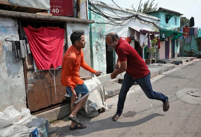A plainclothes policeman wields his baton against a man as a punishment for breaking the lockdown rules, after India ordered a 21-day nationwide lockdown to limit the spreading of coronavirus disease (COVID-19), in Kolkata, India, March 25, 2020. Photo: Reuters