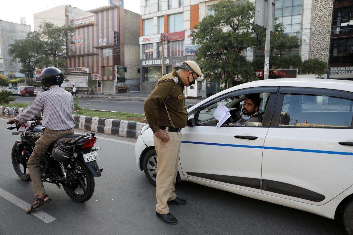 A policeman checks the papers of a driver during a lockdown amid a coronavirus disease (COVID-19) outbreak in New Delhi, India, March 25, 2020.  Photo: Reuters